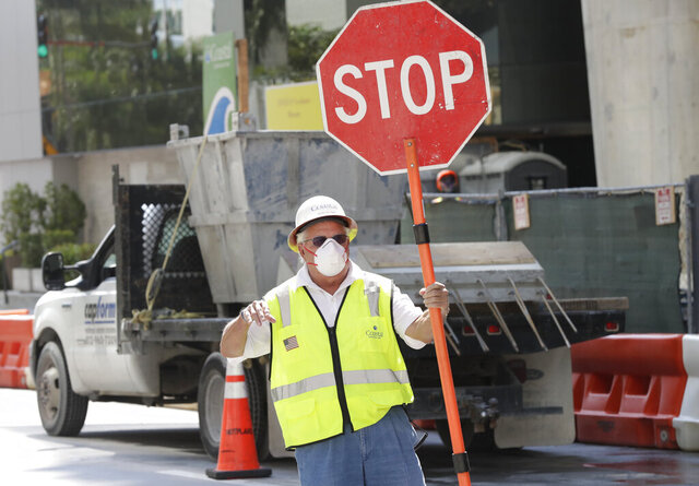A construction worker wears a protective mask as he stops traffic at a construction site in downtown Miami, Thursday, April 9, 2020. The city of Miami mandated Wednesday, that all construction workers on job sites, employees and customers in grocery stores, restaurants, pharmacies and convenience stores must wear masks at all times. (AP Photo/Wilfredo Lee)