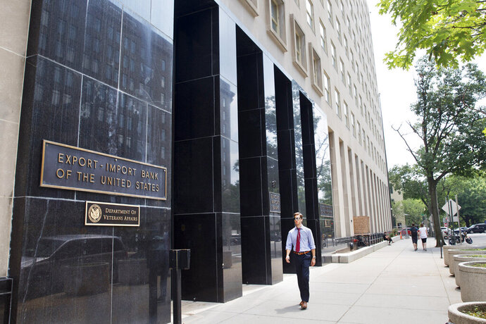 FILE - In this July 28, 2015, file photo,a man walks past the Export-Import Bank of the United States, in Washington. The Democratic-controlled House is on track to pass a measure renewing the charter of the Export-Import Bank, a U.S. agency that provides loans and other help to foreign buyers of U.S. exports. (AP Photo/Jacquelyn Martin)