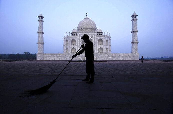 A man sweeps at the Taj Mahal monument early morning in Agra, India, Monday, Sept.21, 2020. The Taj Mahal reopened Monday after being closed for more than six months due to the coronavirus pandemic. (AP Photo/Pawan Sharma)