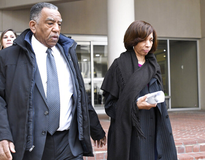 Former Baltimore mayor Catherine Pugh, right, leaves U.S. District Court in Baltimore on Thursday, Nov. 21, 2019. An 11-count federal indictment accuses Pugh of arranging fraudulent sales of her