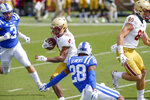 Boston College wide receiver Zay Flowers (4) runs after a catch as Duke Blue cornerback Mark Gilbert (28) tries to make the tackle during the first half of an NCAA college football game, Saturday, Sept. 19, 2020, in Durham, N.C. (Nell Redmond/Pool Photo via AP)