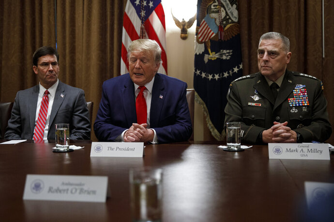 President Donald Trump, joined by from left, Defense Secretary Mark Esper, and Chairman of the Joint Chiefs of Staff Gen. Mark Milley, speaks to media during a briefing with senior military leaders in the Cabinet Room at the White House in Washington, Monday, Oct. 7, 2019. (AP Photo/Carolyn Kaster)