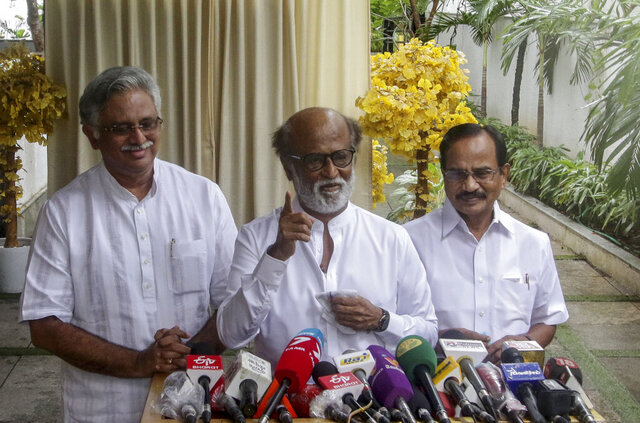 Indian movie superstar Rajinikanth, center, gestures as he addresses a press conference outside his residence in Chennai, India, Thursday, Dec. 3, 2020. Rajinikanth said Thursday he plans to launch his own political party in southern India in January, ending years of speculation by millions of his fans on his political future. (AP Photo/R.Parthibhan)