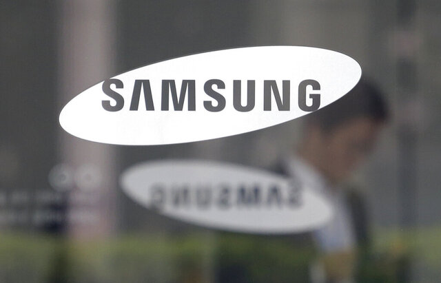 """FILE - In this April 30, 2019 file photo, an employee walks past a logo of the Samsung Electronics Co. at its office in Seoul, South Korea.  Samsung said Tuesday, Feb. 25, 2020,  that a """"technical error"""" displayed customers' personal information on its website to other customers.  The technology company said the error was only on its samsung.com/UK website and affected fewer than 150 customers.  People who logged on to its site were able to see someone else's name, phone number, address, email address and previous orders. Samsung said it did not leak card details. (AP Photo/Ahn Young-joon, File)"""
