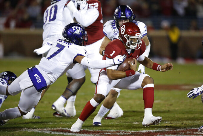 Oklahoma quarterback Jalen Hurts (1) carries past TCU safety Trevon Moehrig (7) and linebacker Garret Wallow (30) in the first quarter of an NCAA college football game in Norman, Okla., Saturday, Nov. 23, 2019. (AP Photo/Sue Ogrocki)