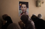 FILE - In this Sunday, Aug. 25, 2019, photo, relatives of Palestinian activist Tamer Sultan, 38 years old, mourn next to a picture of him on a wall in his family home during his funeral in the town of Beit Lahiya, northern Gaza Strip. The death abroad of a Palestinian who fled the Gaza Strip seeking a better life in Europe has highlighted the exodus of thousands of middle-class residents in recent years. Tamer al-Sultan's friends and family say he fled the oppressive rule of Hamas. Others are leaving because of the dire conditions in the territory, which has been under an Israeli and Egyptian blockade since the Islamic militant group seized power 12 years ago. (AP Photo/Khalil Hamra)