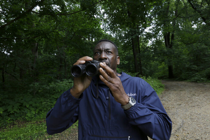 Keith Russell, program manager of urban conservation at Audubon Pennsylvania, lowers his binoculars while conducting a breeding bird census, at Wissahickon Valley Park Friday, June 5, 2020 in Philadelphia. (The viral video of a white woman targeting a Black bird watcher in New York's Central Park has renewed attention to how the great outdoors can often be far from great for Black people. (AP Photo/Jacqueline Larma)