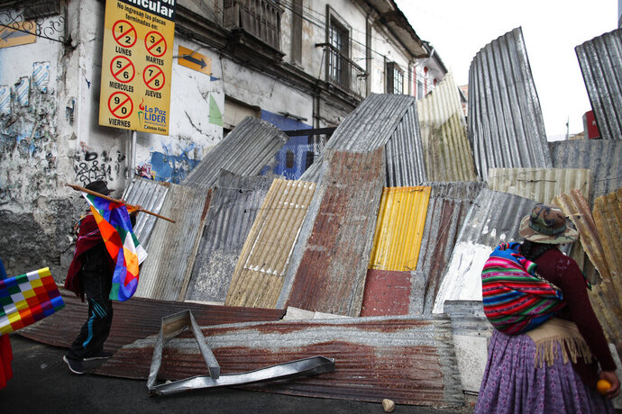 Supporters of former President Evo Morales stand on a barricaded street leading to the presidential palace during a march in La Paz, Bolivia, Thursday, Nov. 14, 2019. Morales resigned and flew to Mexico under military pressure following massive nationwide protests over alleged fraud in an election last month in which he claimed to have won a fourth term in office. (AP Photo/Natacha Pisarenko)