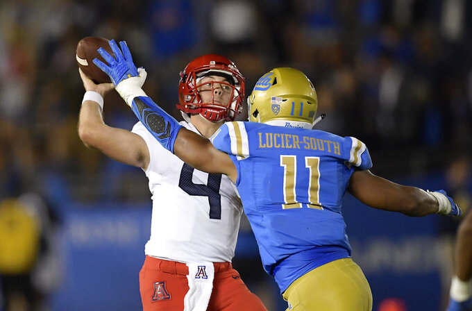 Arizona quarterback Rhett Rodriguez, left, passes while under pressure from UCLA linebacker Keisean Lucier-South during the second half of an NCAA college football game Saturday, Oct. 20, 2018, in Pasadena, Calif. UCLA won 31-30. (AP Photo/Mark J. Terrill)