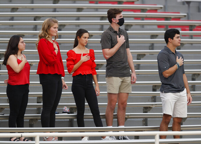 Spectators stand at an NCAA college football game between Texas Tech and Houston Baptist, Saturday, Sept. 12, 2020, in Lubbock, Texas. (AP Photo/Mark Rogers)