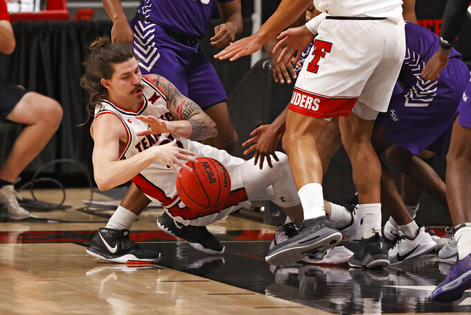 Texas Tech's Avery Benson (21) falls to the court with the rebound during the second half of the team's NCAA college basketball game against Abilene Christian, Wednesday, Dec. 9, 2020, in Lubbock, Texas. (AP Photo/Brad Tollefson)