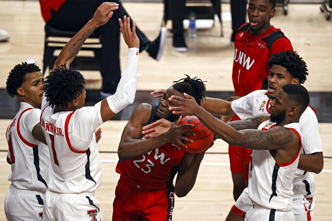 Incarnate Word's Godsgift Ezedinma (23) rebounds the ball around Texas Tech's Terrence Shannon Jr. (1) and Jamarius Burton (2) during the first half of an NCAA college basketball game Tuesday, Dec. 29, 2020, in Lubbock, Texas. (AP Photo/Brad Tollefson)