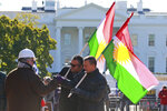 A small group of demonstrators, Diyar, right, and Dijon, center, greet a friend as they hold Kurdistan flags in front of the White House as thy protest the visit of Turkish President Recep Tayyip Erdogan at Lafayette Square in Wednesday, Nov. 13, 2019, in Washington. (AP Photo/Steve Helber)