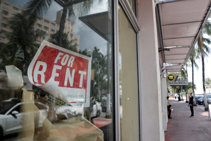FILE - In this July 13, 2020 file photo, a For Rent sign hangs on a closed shop during the coronavirus pandemic in Miami Beach, Fla.  Having endured what was surely a record-shattering slump last quarter, the U.S. economy faces a dim outlook as a resurgent coronavirus intensifies doubts about the likelihood of any sustained recovery the rest of the year. (AP Photo/Lynne Sladky)