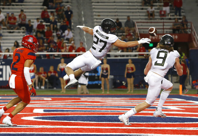 Oregon tight end Jacob Breeland (27) tips the ball as Brenden Schooler (9) makes the catch for the touchdown in the second half during an NCAA college football game against Arizona, Saturday, Oct. 27, 2018, in Tucson, Ariz. (AP Photo/Rick Scuteri)