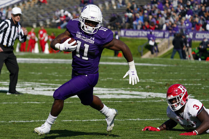 Northwestern running back Andrew Clair, left, runs with the ball past Rutgers linebacker Olakunle Fatukasi during the second half of an NCAA college football game in Evanston, Ill., Saturday, Oct. 16, 2021. Northwestern won 21-7. (AP Photo/Nam Y. Huh)