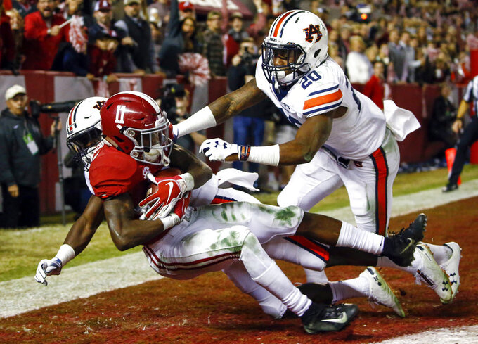 Alabama wide receiver Henry Ruggs III (11) catches a pass for a touchdown as Auburn defensive back Roger McCreary (17) and linebacker Cameron Latu (20) defend during the second half of an NCAA college football game Saturday, Nov. 24, 2018, in Tuscaloosa, Ala. (AP Photo/Butch Dill)