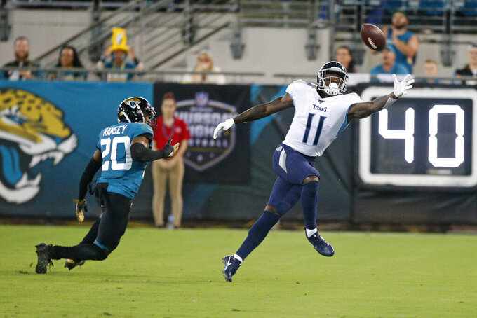 Tennessee Titans wide receiver A.J. Brown (11) reaches for a pass as he is covered by Jacksonville Jaguars cornerback Jalen Ramsey (20) during the first half of an NFL football game, Thursday, Sept. 19, 2019, in Jacksonville, Fla. Brown was called for offensive pass interference on the play. (AP Photo/Stephen B. Morton)