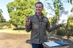 DELETES REFERENCE TO SOLANO COUNTY - California Gov. Gavin Newsom holds up a walnut after signing an executive order on climate change at a news conference at Sierra Orchards walnut farm in Winters, Calif., Wednesday, Oct. 7, 2020. Newsom signed an executive order Wednesday to protect nearly a third of California's land and coastal waters in his latest effort to fight climate change that he has blamed for recent record-breaking wildfires. (Renée C. Byer/The Sacramento Bee via AP, Pool)