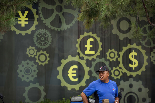 FILE - In this July 20, 2018, file photo, a deliveryman stands near a mural displaying Chinese yuan and other world currency symbols on the outside of a bank in Beijing. The Tokyo Olympics are already the most expensive Summer Games on record with costs set to go higher, a wide-ranging study from Britain's University of Oxford indicates. This is even before the costs of the one-year delay from the COVID-19 pandemic are known with the cost overrun already at over 200%, lead author Bent Flyvbjerg explained in an interview with the Associated Press. (AP Photo/Mark Schiefelbein, File)