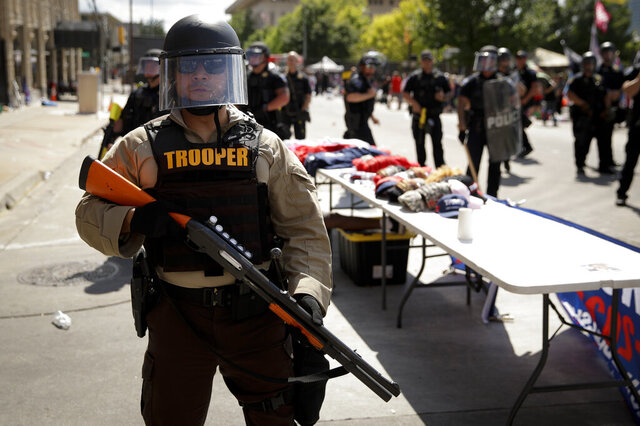 """FILE - In this June 20, 2020, file photo a trooper stands outside the BOK Center where President Trump will hold a campaign rally in Tulsa, Okla. In law enforcement, they're referred to as """"non-lethal"""" tools for crowd control: Rubber bullets. Pepper spray. Batons. Flash-bangs. But the now-familiar scenes of U.S. police officers in riot gear clashing with protesters at Lafayette Park in Washington and elsewhere around the country have police critics charging that the weaponry too often escalates tensions and hurts innocent people. (AP Photo/Charlie Riedel, File)"""