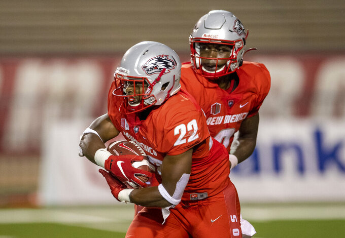 New Mexico running back Aaron Dumas (22) takes a handoff from quarterback Terry Wilson during the second half of an NCAA college football game against Houston Baptist on Thursday, Sept. 2, 2021, in Albuquerque, N.M. (AP Photo/Andres Leighton)