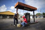 In this Oct. 13, 2019 photo, a gas attendant fills up plastic bottles with gasoline for a customer at a gas station in Chivacoa, Venezuela. Gas is so dirt-cheap that station attendants don't even know the price, and empty handed drivers get waved through, paying nothing at all. (AP Photo/Ariana Cubillos)