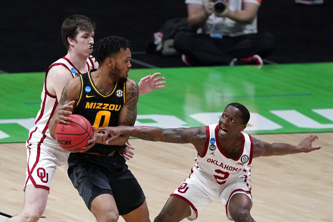 Missouri guard Torrence Watson (0) drives between Oklahoma guard Austin Reaves, left, and guard Umoja Gibson, right, during the first half of a first-round game in the NCAA men's college basketball tournament at Lucas Oil Stadium, Saturday, March 20, 2021, in Indianapolis. (AP Photo/Darron Cummings)