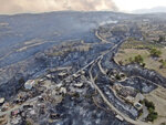 An aerial photo shows destroyed houses in a village as wildfires continue to rage the forests near the Mediterranean coastal town of Manavgat, Antalya, Turkey, Thursday, July 29, 2021. Authorities evacuated homes in southern Turkey as a wildfire fanned by strong winds raged through a forest area near the Mediterranean coastal town of Manavgat. District governor Mustafa Yigit said residents of four neighborhoods were moved out of the fire's path as firefighters worked to control the blaze that broke out Wednesday. It was not immediately clear what caused the fire but authorities said nearby tourist resorts were not affected. (Suat Metin/IHA via AP)