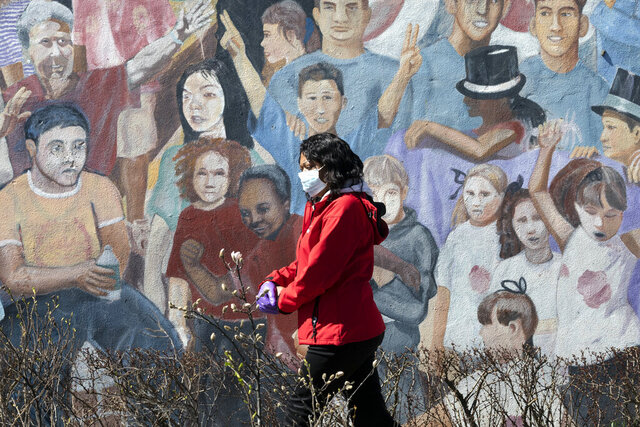 A woman wearing a surgical mask and gloves during the coronavirus outbreak walks past a mural in the Hyde Park neighborhood of Boston, Friday, March 27, 2020. The new coronavirus causes mild or moderate symptoms for most people, but for some, especially older adults and people with existing health problems, it can cause more severe illness or death. (AP Photo/Michael Dwyer)