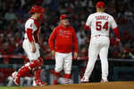 Los Angeles Angels manager Joe Maddon, center, walks to the mound to remove starting pitcher Jose Suarez, right, during the sixth inning of the team's baseball game against the Oakland Athletics in Anaheim, Calif., Saturday, Sept. 18, 2021. At left is catcher Max Stassi. (AP Photo/Alex Gallardo)