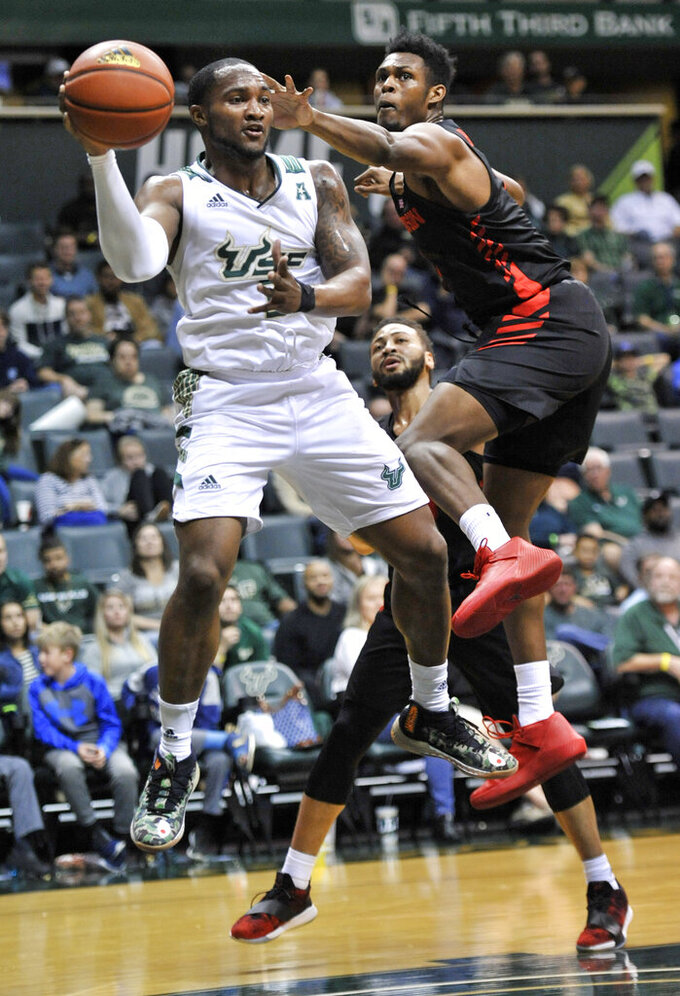 South Florida's Laquincy Rideau, left, grabs a rebound from Houston's Chris Harris Jr., right, and Galen Robinson Jr., center, during the first half of a NCAA college basketball game Saturday, Jan. 19, 2019 in Tampa, Fla. (AP Photo/Steve Nesius)
