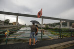 A couple looks at the new San Giorgio Bridge ahead of its inauguration in Genoa, Italy, Monday, Aug. 3, 2020. A large section of the old Morandi bridge collapsed on Aug. 14, 2018, killing 43 people and forcing the evacuation of nearby residents from the densely built-up area. (AP Photo/Luca Bruno)
