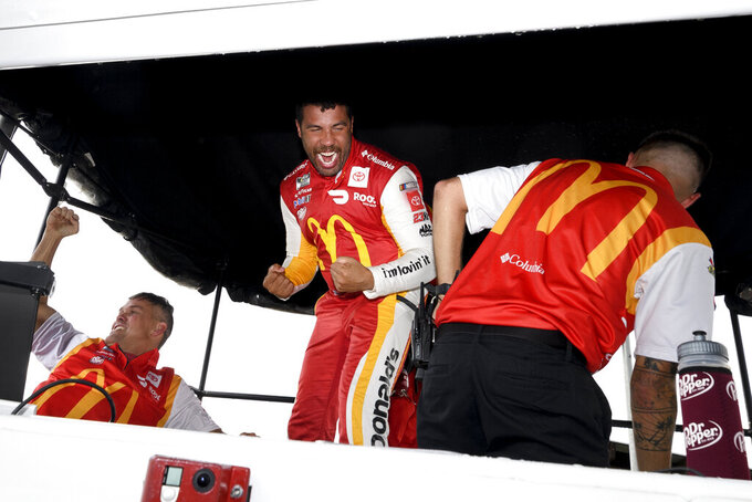 Bubba Wallace, center, and crew react after he is pronounced the winner of a NASCAR Cup series auto race which was stopped for a rain delay, Monday, Oct. 4, 2021, in Talladega, Ala. (AP Photo/John Amis)