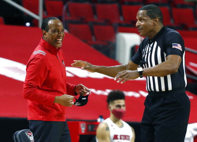 North Carolina State coach Kevin Keatts laughs at a call by official Ted Valentine during the first half of the team's NCAA college basketball game against North Carolina in Raleigh, N.C., Tuesday, Dec. 22, 2020. (Ethan Hyman/The News & Observer via AP)