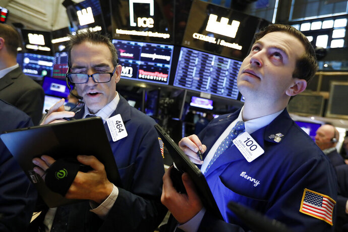 FILE - In this May 9, 2019, file photo traders Gregory Rowe and Benjamin Tuchman work on the floor of the New York Stock Exchange. The U.S. stock market opens at 9:30 a.m. EDT on Friday, May 24. (AP Photo/Richard Drew, File)