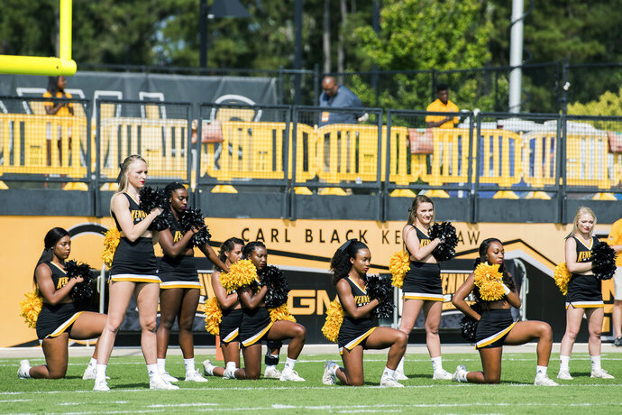 FILE - In this Sept. 30, 2017 photo, five Kennesaw State University cheerleaders take a knee during the national anthem prior to a college football game against North Greenville, in Kennesaw, Ga. Kennesaw State University's decision to remove its cheerleaders from the field after they protested police brutality during the national anthem has cost Georgia taxpayers $145,000 in a legal settlement. Former cheerleader Tommia Dean will get $93,000 of the award, with the rest going to her attorneys. The Marietta Daily Journal obtained a copy of the settlement Wednesday, Dec. 4, 2019, through an Open Records Act request. (Cory Hancock/Atlanta Journal-Constitution via AP, FIle)