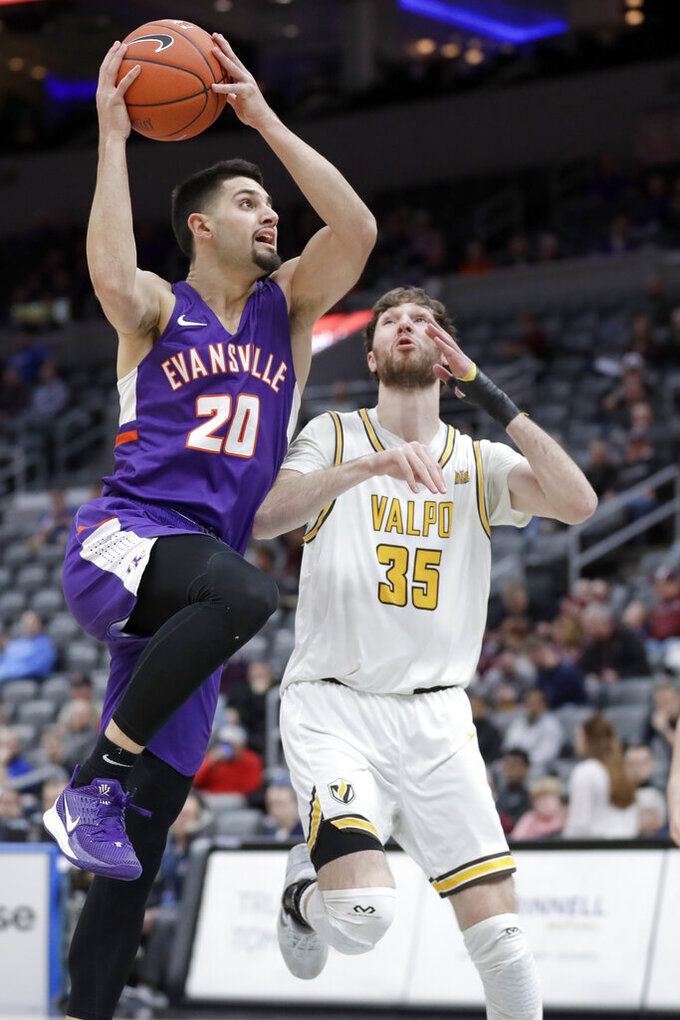 Evansville's Sam Cunliffe (20) heads to the basket as Valparaiso's Ryan Fazekas (35) defends during the first half of an NCAA college basketball game in the first round of the Missouri Valley Conference men's tournament Thursday, March 5, 2020, in St. Louis. (AP Photo/Jeff Roberson)