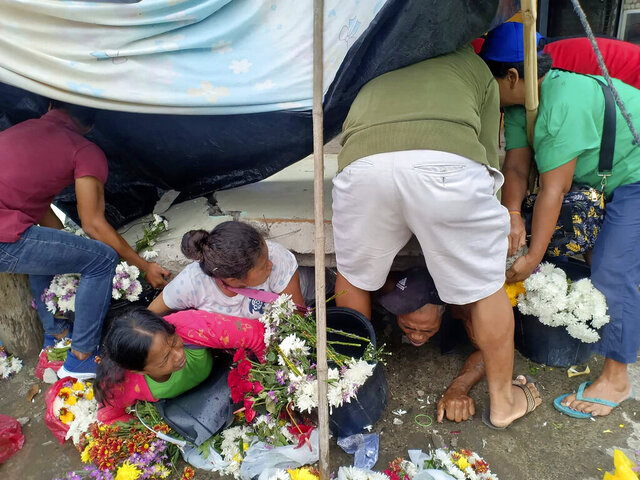 Trapped flower vendors are pulled out from a collapsed wall following an earthquake that struck Padada, Davao del Sur province, southern Philippines on Sunday Dec. 15, 2019. A strong quake jolted the southern Philippines on Sunday, causing a three-story building to collapse and prompting people to rush out of shopping malls, houses and other buildings in panic, officials said. (AP Photo/John Angelo Jomao-as)