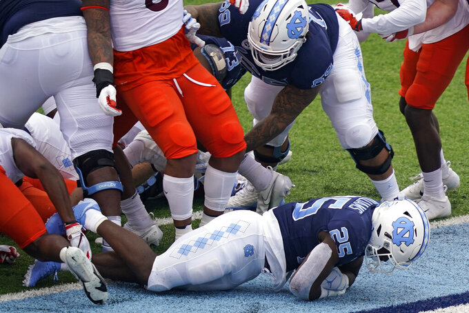 North Carolina running back Javonte Williams (25) scores a touchdown against Virginia Tech during the first half of an NCAA college football game in Chapel Hill, N.C., Saturday, Oct. 10, 2020. (AP Photo/Gerry Broome)