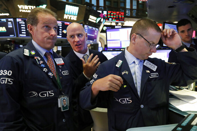 Specialists Glenn Carell, left, John 'Hara, center, and Robert Nelson, gather at a trading post on the floor of the New York Stock Exchange, Wednesday, Aug. 14, 2019. The Dow Jones Industrial Average sank 800 points after the bond market flashed a warning sign about a possible recession for the first time since 2007. (AP Photo/Richard Drew)