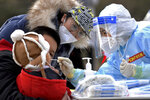 In this photo released by Xinhua News Agency, a medical staff in a protective suit takes a swab from a child near a residential area in Shijiazhuang in northern China's Hebei Province on Sunday, Jan. 10, 2021. Chinese health authorities say scores more people have tested positive for coronavirus in Hebei province bordering on the capital Beijing. The outbreak focused on the Hebei cities of Shijiazhuang and Xingtai is one of China's most serious in recent months and comes amid measures to curb the further spread during next month's Lunar New Year holiday. (Wang Xiao/Xinhua via AP)