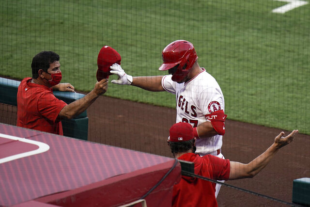 Los Angeles Angels' Mike Trout celebrates his two-run home run with coaches as he returns to the dugout during the first inning of the team's baseball game against the Houston Astros, Friday, Sept. 4, 2020, in Anaheim, Calif. (AP Photo/Jae C. Hong)
