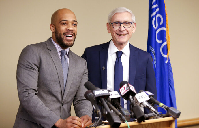 FILE - In this Jan. 3, 2019 file photo, Wisconsin Lt Gov-elect Mandela Barnes, left, and Democratic Gov-elect Tony Evers address the media in Madison, Wis. A new report shows that Wisconsin's Democratic Lt. Gov. Barnes has far more security than his Republican predecessor. The online publication WisPolitics.com reported Monday, May 13, 2019, that the State Patrol's Dignitary Protection Unit spent nine times as many hours protecting Barnes over a two-month period as it did his predecessor, Rebecca Kleefisch, in all of 2018. Barnes is the state's first African American lieutenant governor.(Steve Apps/Wisconsin State Journal via AP, File)