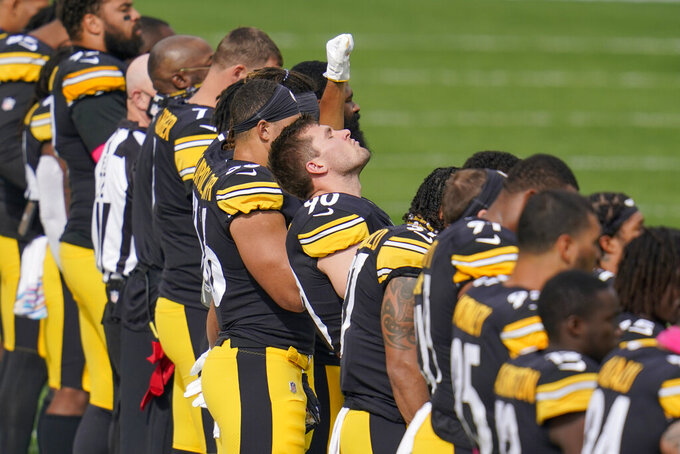 A Pittsburgh Steelers player raises a fist as he stands in line with the team during the playing of the national anthem before an NFL football game against the Cleveland Browns, Sunday, Oct. 18, 2020, in Pittsburgh. (AP Photo/Gene J. Puskar)
