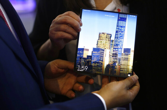 FILE - In this Tuesday, Feb. 26, 2019 file photo, a man holds the new Huawei Mate X foldable 5G smartphone during the Mobile World Congress wireless show, in Barcelona, Spain. Two British mobile phone companies, EE and Vodafone, said Wednesday May 22, 2019, they are putting on hold plans to sell new 5G mobile phones from China's Huawei. (AP Photo/Manu Fernandez, File)