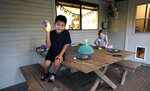 Byron Xol, left, an immigrant from Guatemala, plays with a bubble gun as he sits outside with Desmond Sewell Monday, June 24, 2019, in Buda, Texas. After spending more than a year in federal facilities, Byron has been living with the Sewells in recent months. His father, David, was deported to Guatemala. He says he and his son left that country because they had been threatened by gangsters. (AP Photo/David J. Phillip)