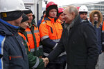 Russian President Vladimir Putin, right, greets workers as he attends an opening ceremony of the road junction of the M-10