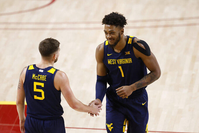 West Virginia guard Jordan McCabe, left, high fives forward Derek Culver, right, after a Iowa State turnover during the second half of an NCAA college basketball game, Tuesday, Feb. 2, 2021, in Ames, Iowa. West Virginia won 76-72. (AP Photo/Matthew Putney)