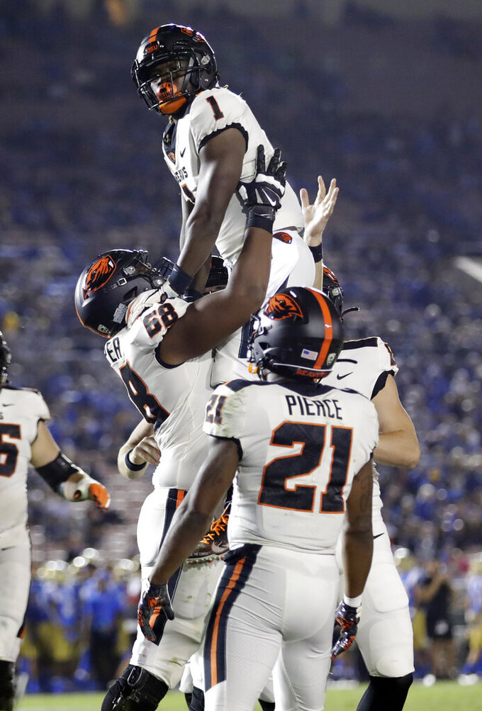 Oregon State wide receiver Tyjon Lindsey (1) is lifted by teammates after catching a touchdown pass against UCLA during the second half of an NCAA college football game Saturday, Oct. 5, 2019, in Pasadena, Calif. (AP Photo/Marcio Jose Sanchez)